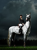 Young woman on grey horse