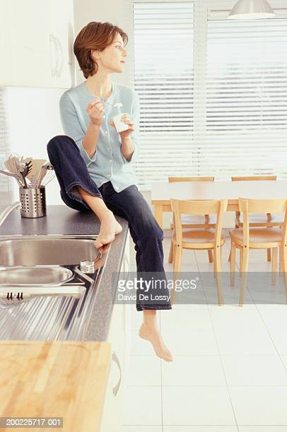 Young woman on kitchen bench eating yoghurt