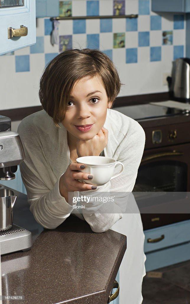 Mujer joven en mostrador de cocina sosteniendo taza de té : Foto de stock