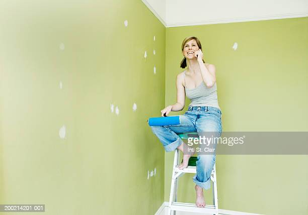 Young woman on ladder, holding paint roller, using mobile phone
