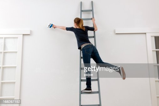 young woman on ladder painting white wall