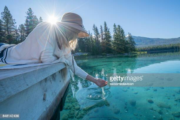 Young woman on lake pier catching fresh water from mountain lake