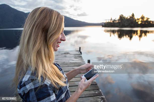 Young woman on lake pier text messaging on smartphone
