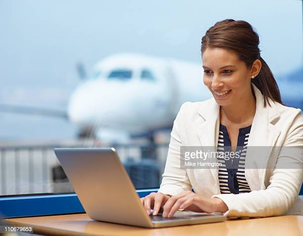 Young Woman On Laptop In Airport Cafe