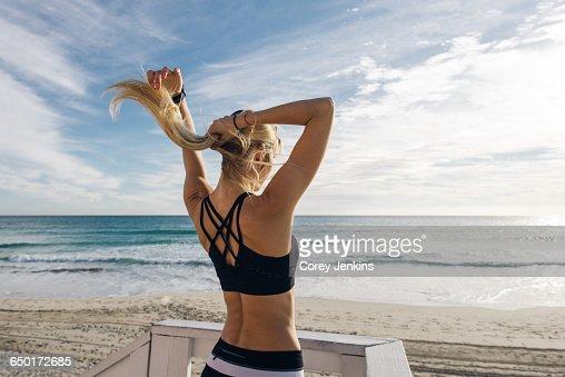 Young woman on lifeguard platform, putting hair up, rear view