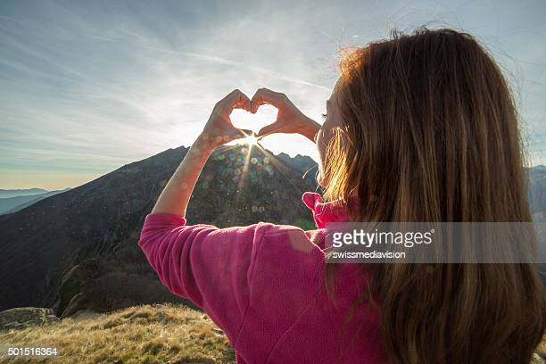 Young woman on mountain top makes heart shape finger frame