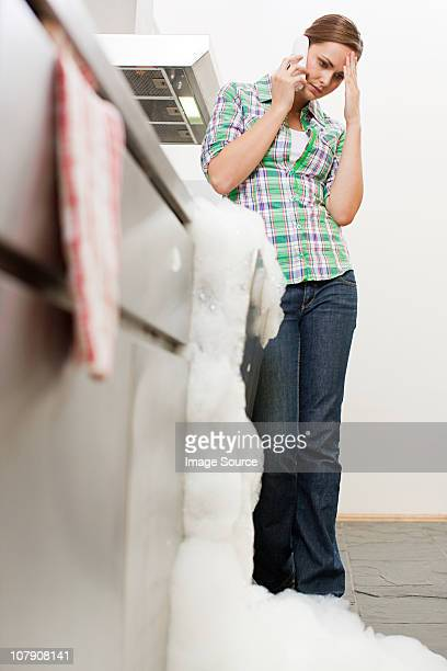 Young woman on phone with overflowing dishwasher