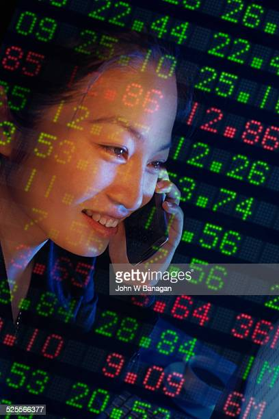 Young woman on phone with stock market data