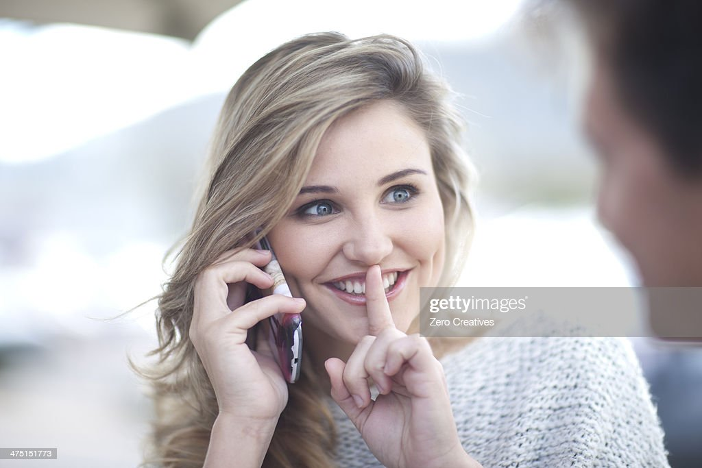 Young woman on phonecall with finger to lips : Stock Photo