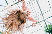 A low angle view of a young woman hanging from monkey bars on a playground and smiling at the camera. Horizontal shot.