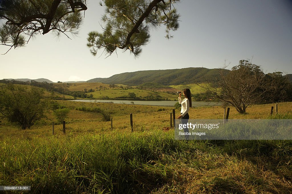 Young woman on ranch using binoculars, side view : Stock Photo