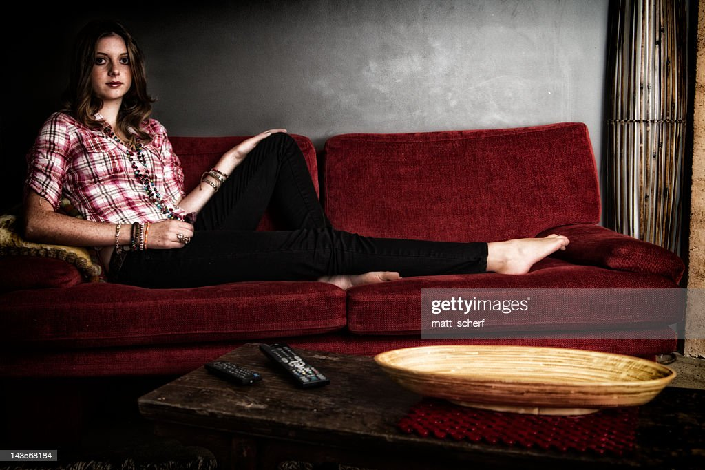 Young Woman On Red Sofa : Stock Photo