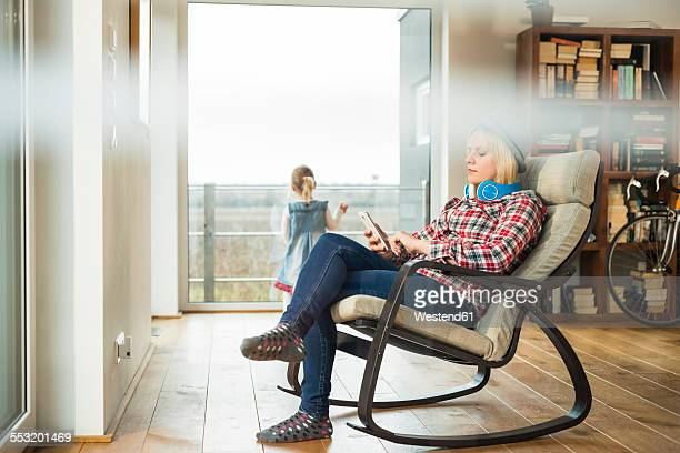 Young woman on rocking chair using digital tablet with girl in background