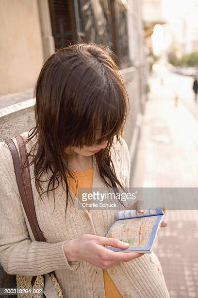Young woman on sidewalk, looking at map in guidebook