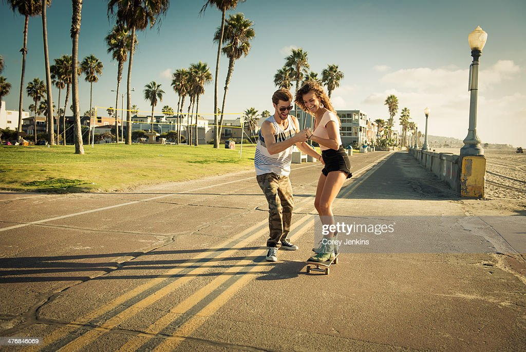 Young woman on skateboard at San Diego beach, boyfriend helping : Stock Photo