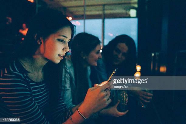 Joven mujer mira en smartphone, iluminado horizonte de la ciudad de fondo
