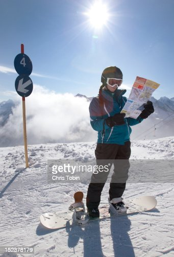 Young woman on snowboard looking at map : Bildbanksbilder