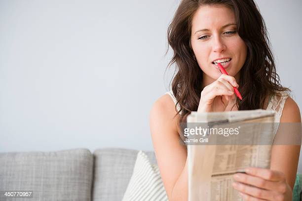 Young woman on sofa doing crossword puzzle