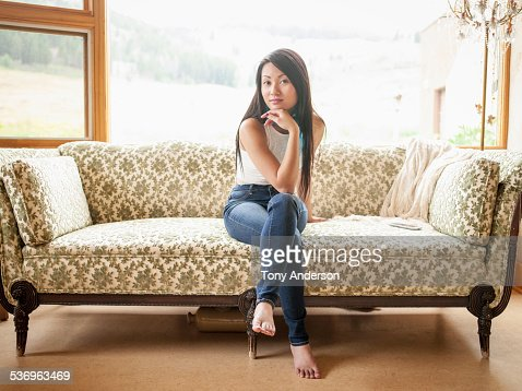 Young woman on sofa near window at home