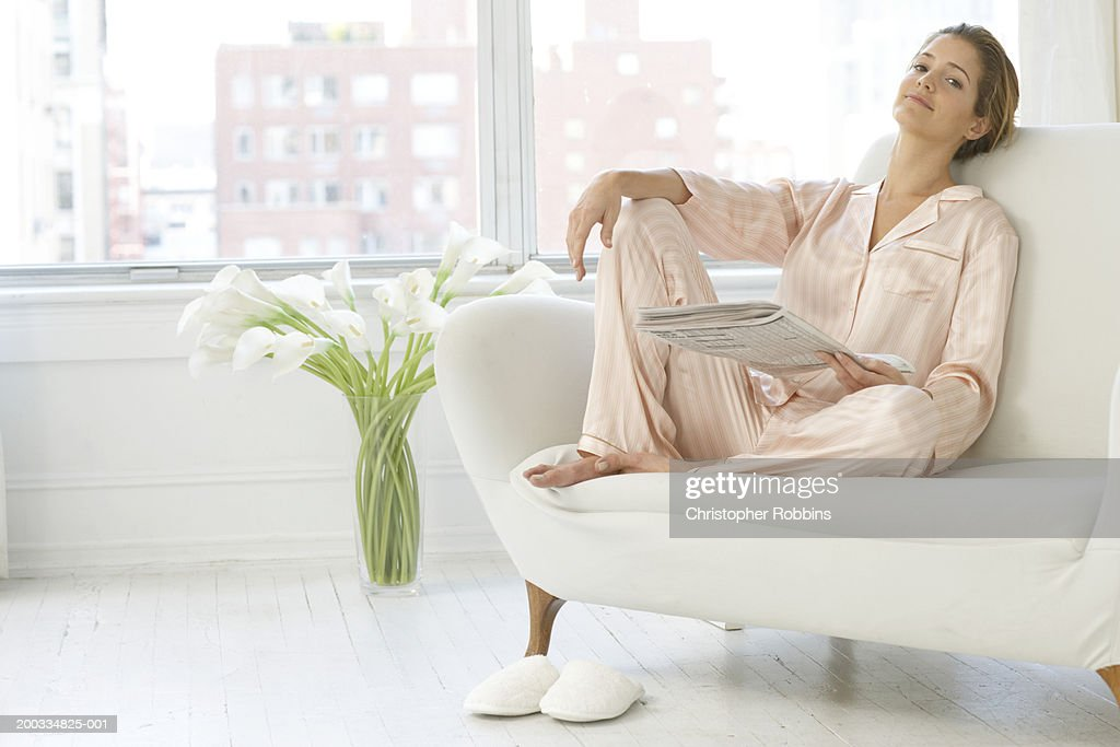 Young woman on sofa, wearing pyjamas and holding newspaper, portrait : Stock Photo