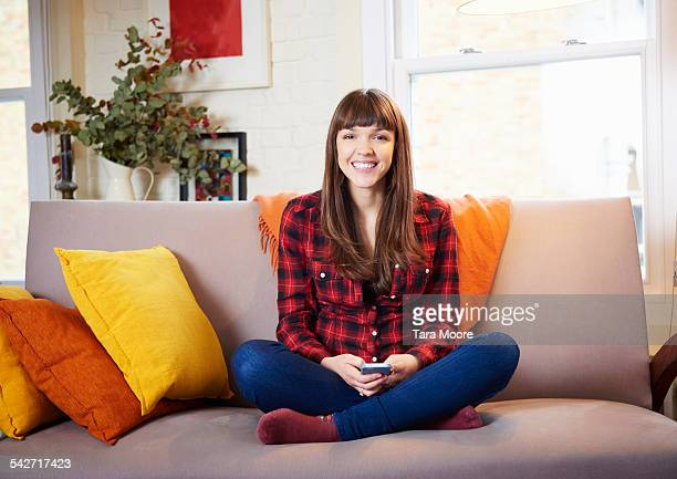 Young woman on sofa with mobile