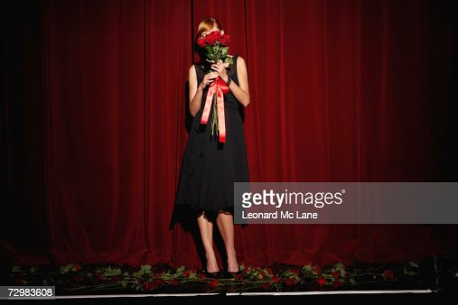 'Young woman on stage holding red roses, low section'