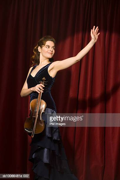 Young woman on stage holding violin and waving hand
