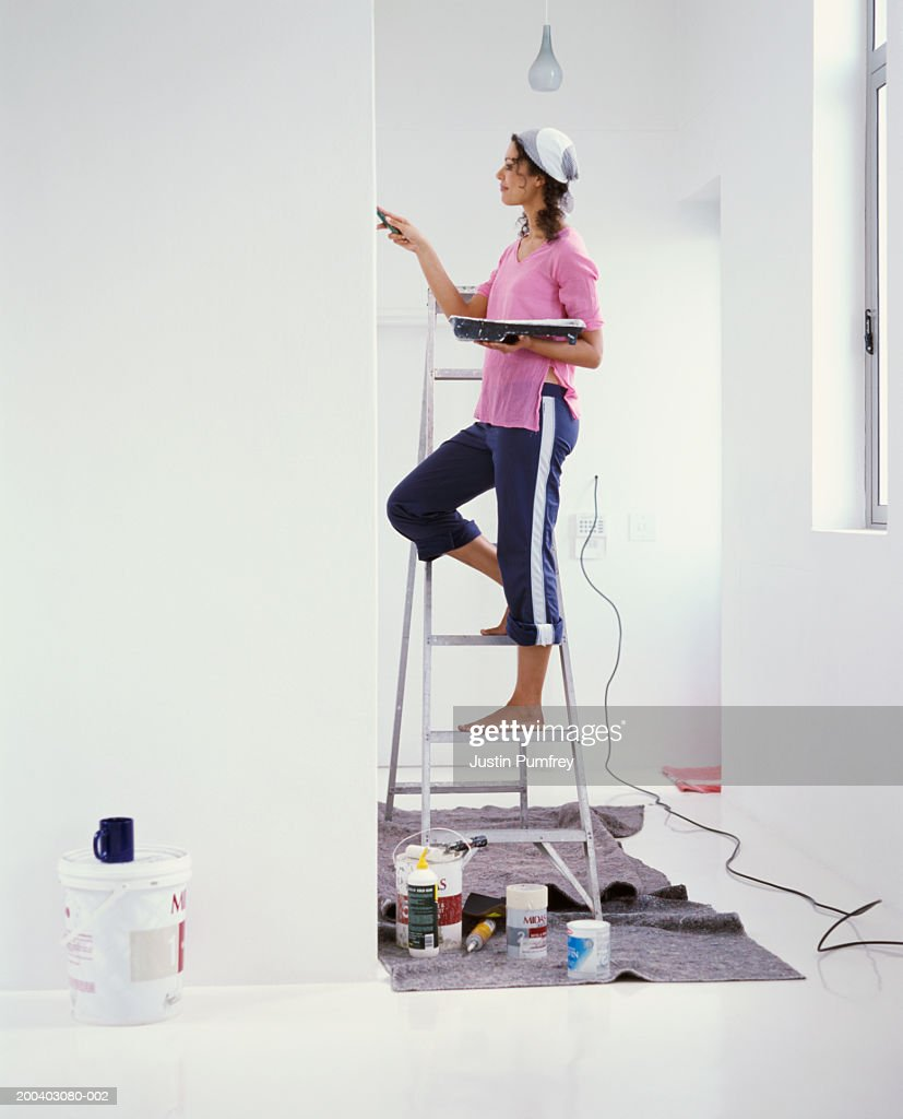 Young woman on stepladder painting wall, side view : Stock Photo