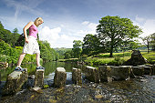 Young woman on stepping stones over River Rothay