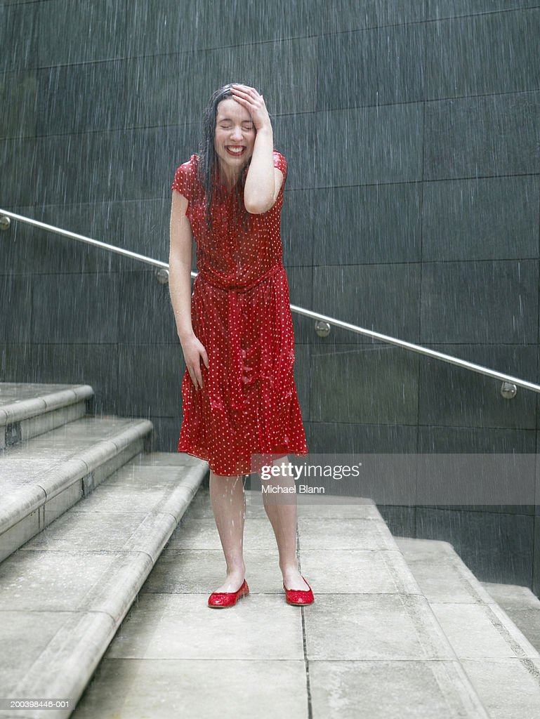 Young woman on steps in rain, hand resting on head, eyes closed