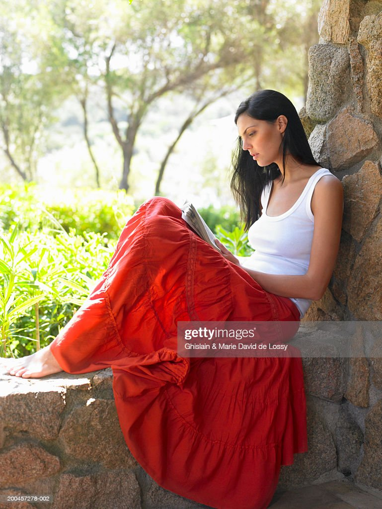 Young woman on stone ledge reading, side view : Stock Photo