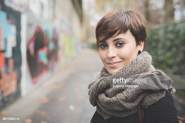Young woman on street, graffiti wall in background