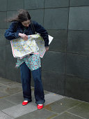 Young woman on street holding map, looking down, hair blowing in wind