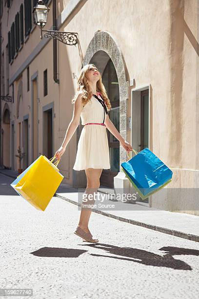 Young woman on street with shopping bags, looking up