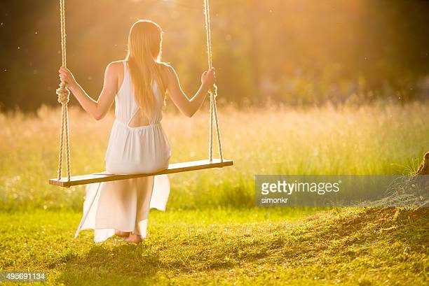 Young woman on swing at sunset