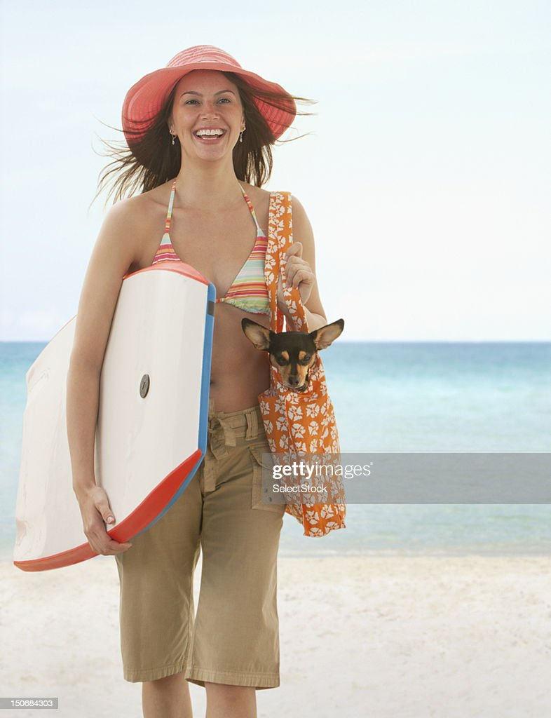 Young woman on the beach holding small dog and boogie board : Stock Photo