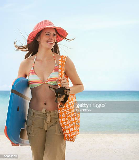 Young woman on the beach holding small dog and boogie board