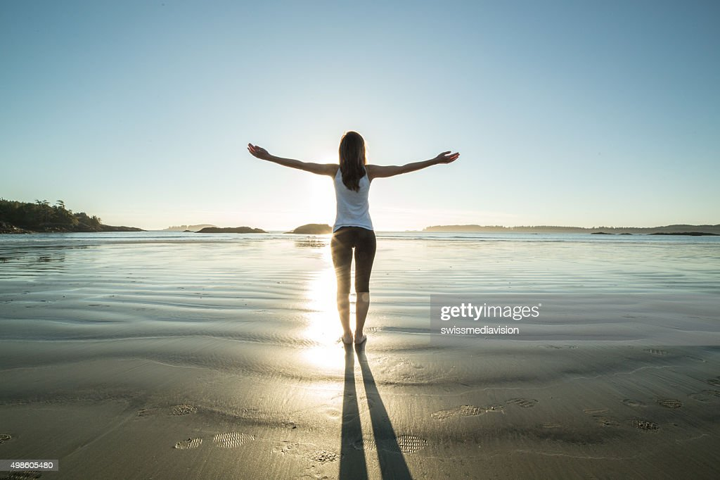 Young woman on the beach in autumn arms outstretched : Stock Photo