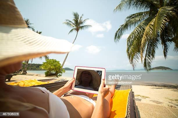 Jeune femme sur la plage à l'aide de Tablette numérique