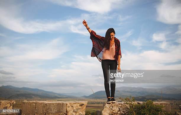 Mujer joven en el pico de la montaña de