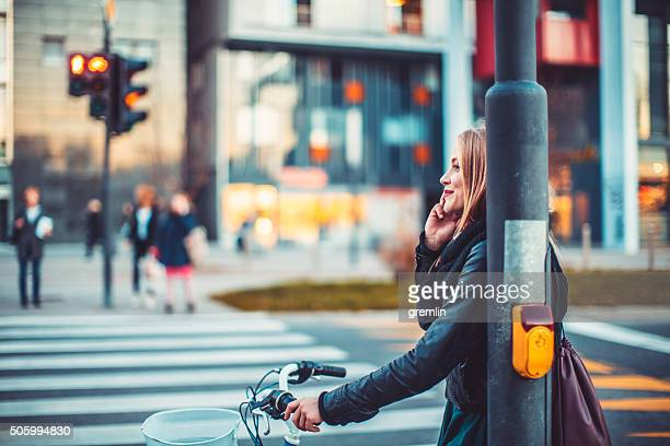 Jovem mulher com telefone, morada, pôr do sol