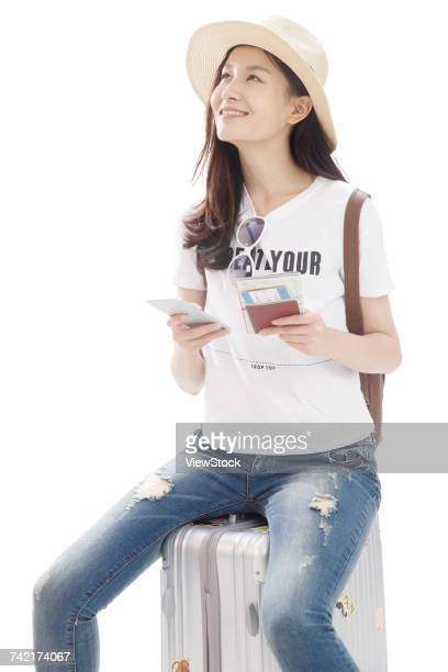 Young woman on travel sitting on suitcase