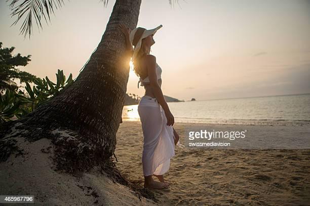 Giovane donna sulla spiaggia tropicale al tramonto godendo