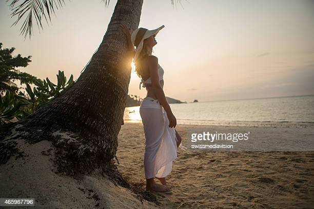 Young woman on tropical beach enjoying sunset
