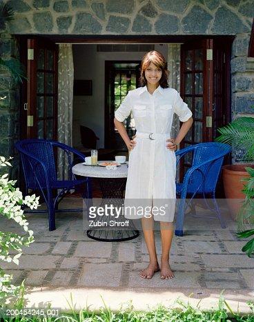 Young woman on verandah smiling, portrait : Stock Photo