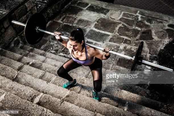 Young woman on weight training doing squats in open space