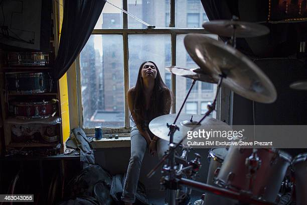 Young woman on window seat of New York apartment