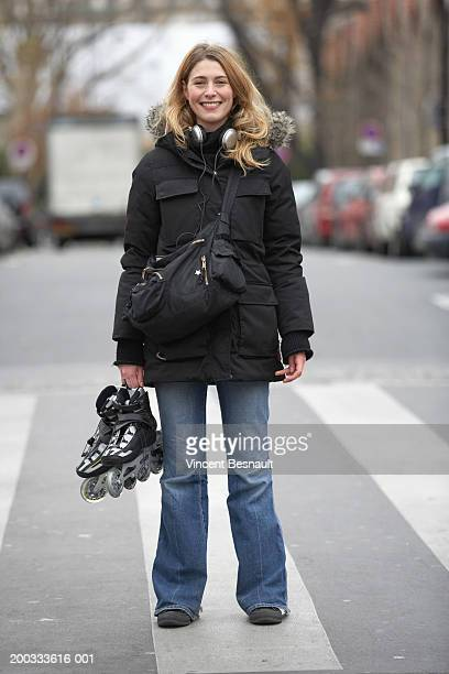 Young woman on zebra crossing holding roller skates, smiling, portrait