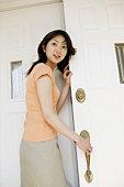 Young Woman Opening Door