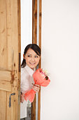 Young Woman Opening Door with Holding Bouquet